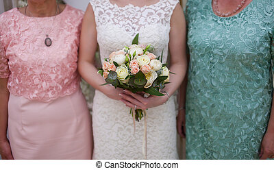 Hands of bride holding a bouquet of roses. Photo with parents
