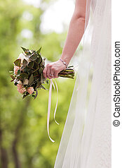 Hands of bride holding a bouquet of roses