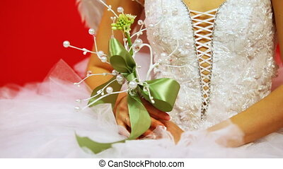 hands of bride in wedding dress holding bouquet decorated with pearls