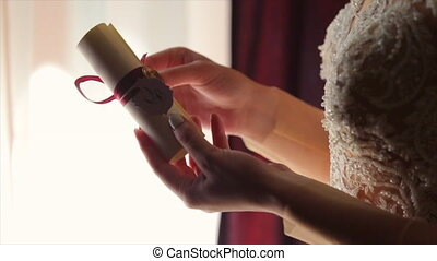 Hands of Bride Rolling Out a Wedding Invitation - Hands nad...