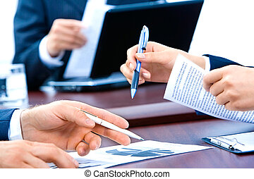 Close-up of business people�s hands holding pens and documents at meeting