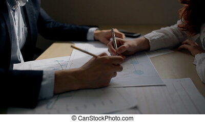Hands of businessman and businesswoman working on financial graph in the office