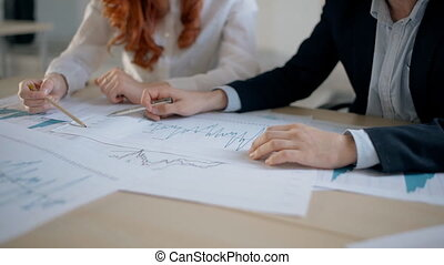 Hands of businessman in suit and businesswoman in white shirt working on financial graphs