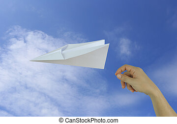 Hands of businessman throwing a paper plane on blue sky background.