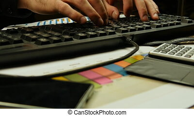 Hands of businessman typing on a keyboard and sign a document