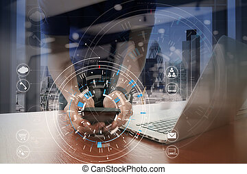 Hands of businessman using mobile phone in modern office with laptop and digital tablet computer with VR icon diagram
