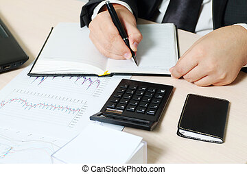 Hands of businessman writing in notebook at table with laptop, documents, tablet PC, calculator