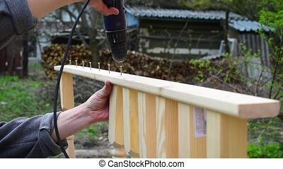 Hands of carpenter affixing pine wood banisters to a plank -...