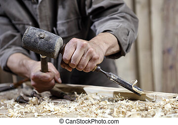 hands of carpenter with a hammer and chisel on the workbench...