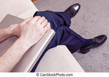 Hands of Caucasian Male Holding Laptop. Sitting on Couch Indoors.