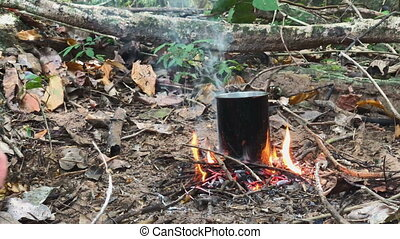 Hands of Caucasian Savage Man Burning Little Campfire in the...