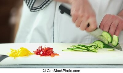 Hands of chef cutting cucumber.
