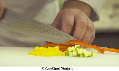 Hands of chef cutting up a paprika with a knife - Cooking in...