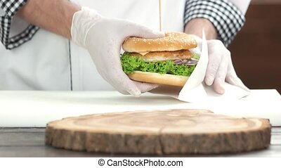 Hands of chef holding burger. Fast food dish.