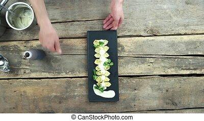 Hands of chef, Italian food. Ravioli on wooden background.