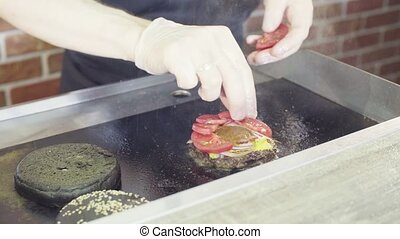 Hands of chef putting tomatos on a grilled burger