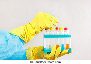 Hands of chemist in rubber gloves doing chemical analysis in laboratory