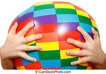 Hands of child hold big, bright, multi-coloured, inflatable ball. A close up. Isolated on white background.