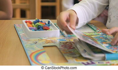 Hands of child learning letters during lesson