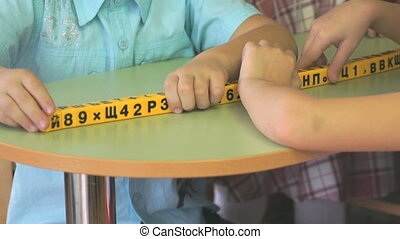 Hands of children studying numbers and letters - Hands of...