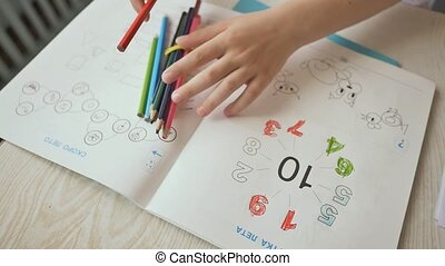 Hands of children who draw with pencils in kindergarten. Close-up.
