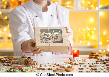 Hands of confectioner showing a box with gingerbread cookies