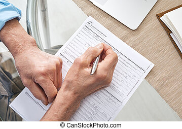 Hands of contemporary senior retired man filling in health insurance form
