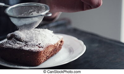 Hands of cook adding powdered sugar on the peice pie - Slow...