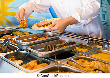 Hands of cook putting in plate vegetable ragout in public catering restaurant