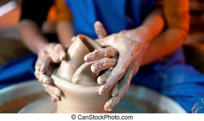 Hands of couple breaks clay jug on potter's wheel. Fun,...