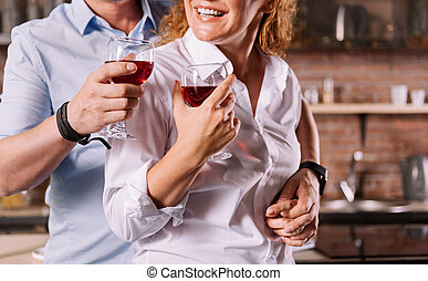Hands of couple holding glasses