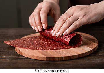 Hands of creative housewife rolling homemade fruit leather on wooden board