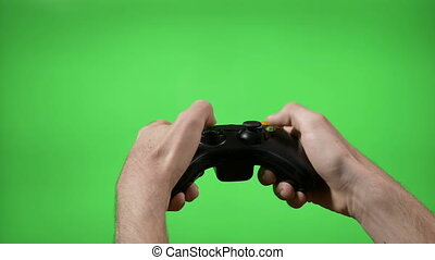 Hands of dedicated young gamer using a game controller with green screen in background