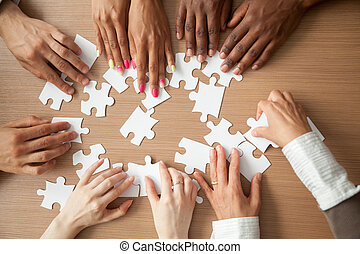Hands of diverse people assembling jigsaw puzzle together, top v