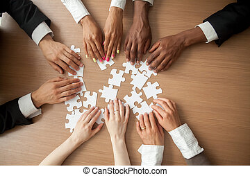 Hands of diverse people connecting puzzle together, top closeup
