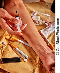 Hands of drug addict with tourniquet and syringe.