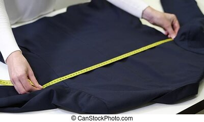 Hands of dry-cleaning employee measuring jacket - Close-up...