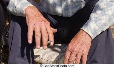 Hands of elderly homeless man smoking a cigarette