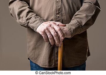 Hands of elderly male holding cane