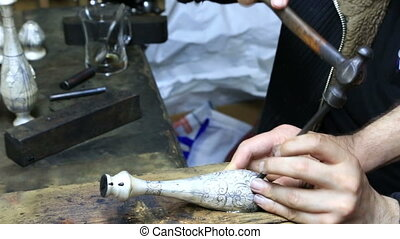 Hands of engraver working with silver vessel - Professional...