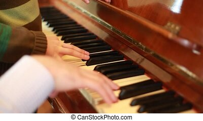 Hands of father and son playing on piano