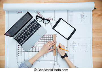 Hands of female architect drawing blueprint