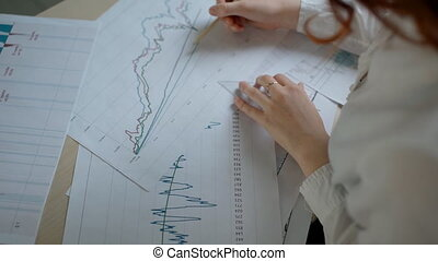 Hands of female financial analytic in white shirt drawing...