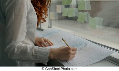 Hands of female financial analytic in white shirt working...
