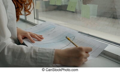 Hands of female financial analytic working on paper graphs near the office window