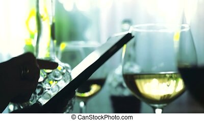 Hands of female uses smartphone and glasses of white wine....