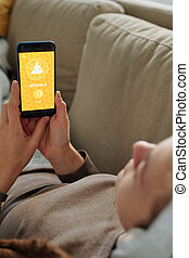 Hands of female with smartphone going to take session of online yoga course