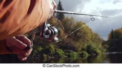Hands of fisherman casting fishing rod and reeling it. - ...