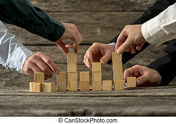 Hands of five businessman holding wooden blocks placing them into a structure