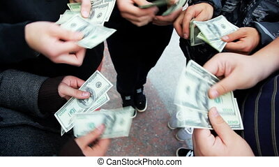 hands of five men recount number of dollars and show closer...
